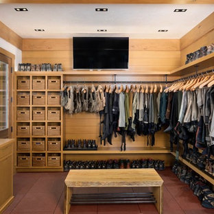 This is an example of a large country mudroom in Denver with brown walls, vinyl floors, a single front door, a light wood front door and red floor.