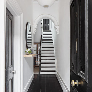 This is an example of a large contemporary entry hall in Melbourne with white walls, a single front door, a black front door and black floor.