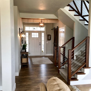 Inspiration for a large farmhouse vinyl floor and brown floor entryway remodel in Other with gray walls and a white front door