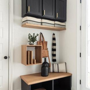 ダラスの小さい引き戸モダンスタイルのおしゃれなマッドルーム (白い壁、淡色無垢フローリング、黒いドア) の写真