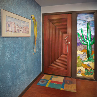 Example of an eclectic medium tone wood floor and brown floor entryway design in Phoenix with blue walls and a medium wood front door
