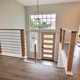 Idées déco pour un hall d'entrée campagne de taille moyenne avec un mur gris, sol en stratifié, une porte simple, une porte en bois brun et un sol gris.