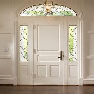 Exempel på en mycket stor klassisk ingång och ytterdörr, med vita väggar, mörkt trägolv, en enkeldörr och en vit dörr