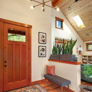Aménagement d'une porte d'entrée montagne avec un mur blanc, une porte simple, une porte en bois brun, un sol en bois brun et un sol marron.
