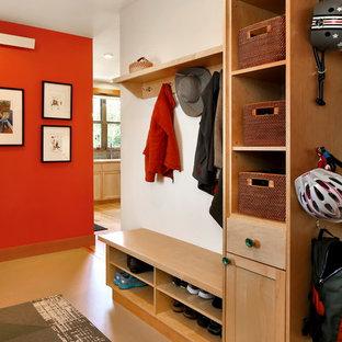 Amerikansk inredning av ett kapprum, med röda väggar, linoleumgolv, en enkeldörr, mellanmörk trädörr och beiget golv