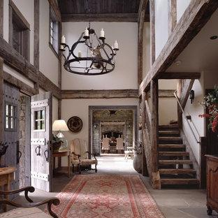 Cette image montre un hall d'entrée chalet avec un mur blanc, une porte double et une porte en bois brun.