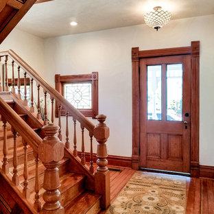 На фото: фойе среднего размера в классическом стиле с белыми стенами, паркетным полом среднего тона, одностворчатой входной дверью, входной дверью из дерева среднего тона и оранжевым полом с