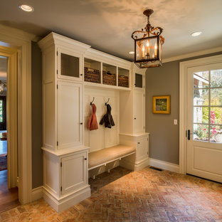 Cette photo montre une grand entrée chic avec un sol en brique, un vestiaire, un mur gris, une porte simple et une porte blanche.