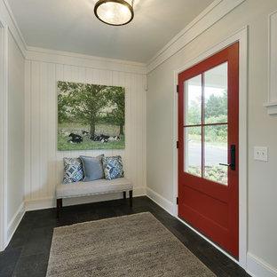 Aménagement d'une porte d'entrée campagne de taille moyenne avec un mur gris, un sol en ardoise, une porte simple, une porte rouge et un sol gris.