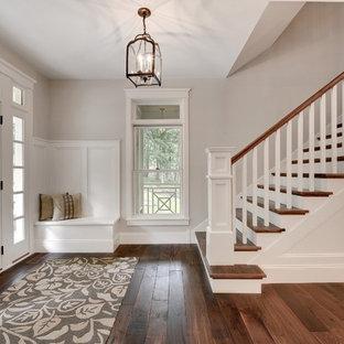 ミネアポリスの中くらいの片開きドアトランジショナルスタイルのおしゃれな玄関ロビー (白いドア、グレーの壁、濃色無垢フローリング、茶色い床) の写真