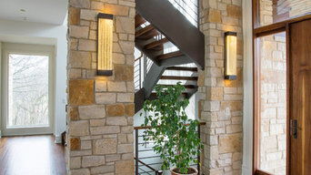 Foyer Featuring Stone Columns and Floating Open Tread Walnut Staircase with Waln