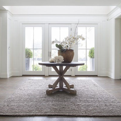 Example of a large transitional dark wood floor entryway design in New York with white walls and a glass front door