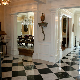 Entryway - large traditional marble floor entryway idea in New York with white walls and a medium wood front door
