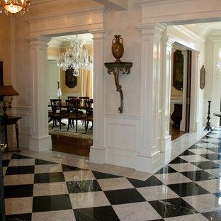 На фото: большое фойе в классическом стиле с белыми стенами, мраморным полом, двустворчатой входной дверью и входной дверью из дерева среднего тона