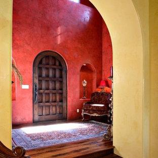 Cette photo montre un très grand hall d'entrée méditerranéen avec un mur rouge, un sol en bois foncé et une porte simple.