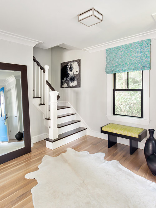 example of a foyer design in new york with gray walls and medium tone hardwood