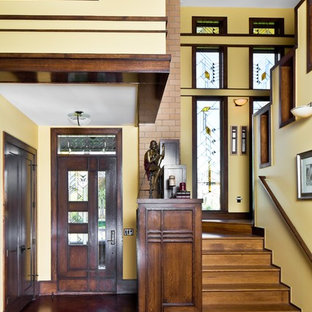 Example of an arts and crafts entryway design in Denver with yellow walls