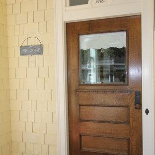 Immagine di una porta d'ingresso vittoriana con pareti gialle, pavimento in legno verniciato, una porta singola, una porta in legno bruno e pavimento rosso