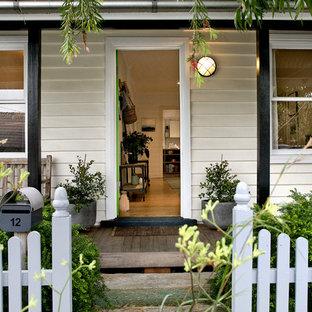 Traditional front door in Sydney with white walls, medium hardwood floors, a single front door and brown floor.