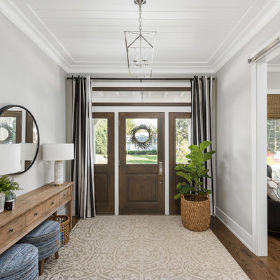 Example of a large transitional brown floor and dark wood floor entryway design in Chicago with gray walls and a dark wood front door