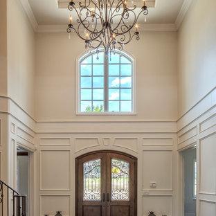 На фото: большое фойе с белыми стенами, паркетным полом среднего тона, двустворчатой входной дверью, коричневой входной дверью и коричневым полом
