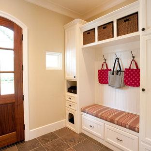 На фото: большой тамбур в классическом стиле с бежевыми стенами, полом из сланца, одностворчатой входной дверью, входной дверью из дерева среднего тона и правильным освещением с