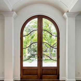 Inredning av en mycket stor ingång och ytterdörr, med vita väggar, mellanmörkt trägolv, en dubbeldörr, mellanmörk trädörr och brunt golv
