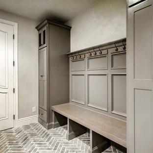 Cette photo montre une grand entrée avec un vestiaire, un mur gris, un sol en brique et un sol gris.