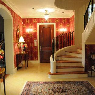 マイアミの片開きドアおしゃれな玄関ロビー (赤い壁、トラバーチンの床、濃色木目調のドア) の写真
