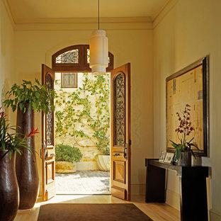 На фото: прихожая в средиземноморском стиле с двустворчатой входной дверью и входной дверью из дерева среднего тона с