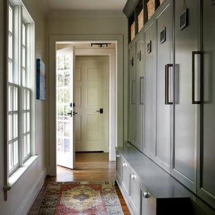 Exempel på ett mellanstort klassiskt kapprum, med beige väggar, mellanmörkt trägolv, en enkeldörr, glasdörr och brunt golv