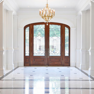 Large elegant marble floor and white floor entryway photo in New York with beige walls and a medium wood front door