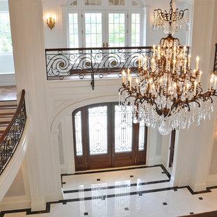 На фото: большое фойе в классическом стиле с бежевыми стенами, мраморным полом, двустворчатой входной дверью, входной дверью из дерева среднего тона и белым полом