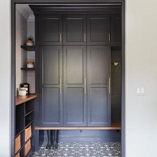 Cette image montre une entrée marine de taille moyenne avec un vestiaire, un mur gris, un sol en carrelage de porcelaine, une porte simple, une porte grise et un sol multicolore.