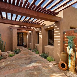 フェニックスの中サイズの片開きドアサンタフェスタイルのおしゃれな玄関ドア (ベージュの壁、テラコッタタイルの床、濃色木目調のドア、ベージュの床) の写真