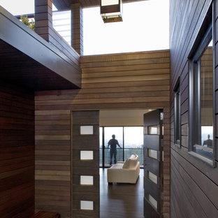 Idée de décoration pour une porte d'entrée minimaliste avec une porte simple et une porte en bois foncé.