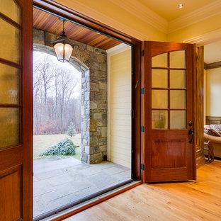 Large elegant light wood floor entryway photo in DC Metro with yellow walls and a medium wood front door