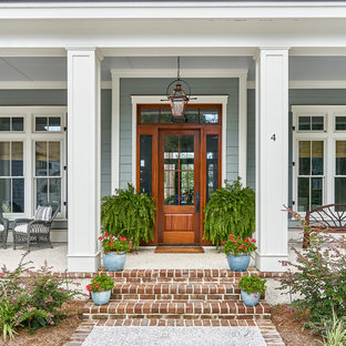 Example of a large coastal entryway design in Charleston with a medium wood front door and blue walls