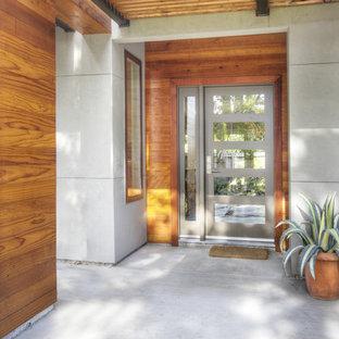 Bild på en mellanstor funkis ingång och ytterdörr, med en grå dörr, grå väggar, betonggolv, en enkeldörr och grått golv