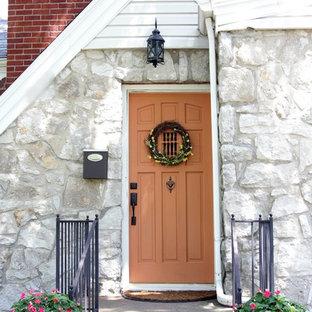 Foto di una porta d'ingresso tradizionale con una porta singola e una porta arancione