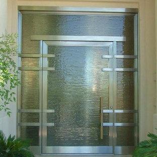 Cette image montre une grand porte d'entrée minimaliste avec une porte simple, une porte en verre, un mur beige et un sol en travertin.