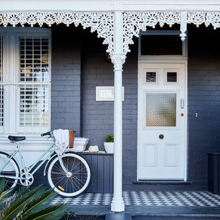 Example of a mid-sized classic porcelain floor and black floor entryway design in Sydney with black walls and a white front door