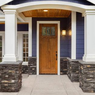 Exempel på en mellanstor amerikansk ingång och ytterdörr, med lila väggar, betonggolv, en enkeldörr och mellanmörk trädörr