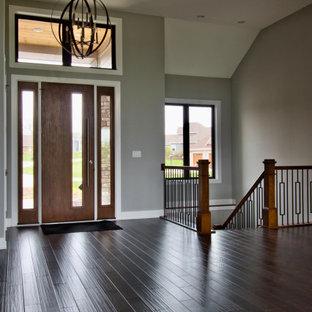 ミルウォーキーの広い片開きドアモダンスタイルのおしゃれな玄関ロビー (グレーの壁、濃色無垢フローリング、濃色木目調のドア、茶色い床、折り上げ天井) の写真