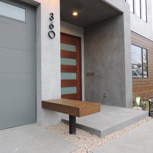 Inredning av en modern ingång och ytterdörr, med grå väggar, en enkeldörr, mörk trädörr, betonggolv och grått golv