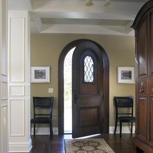Modelo de entrada tradicional, grande, con paredes beige, suelo de madera oscura, puerta simple y puerta de madera oscura