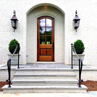 Diseño de puerta principal clásica, de tamaño medio, con puerta simple, puerta de madera en tonos medios, paredes blancas, suelo de pizarra y suelo gris