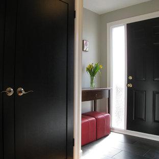 Klassisk inredning av en entré, med en svart dörr och svart golv