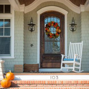 Ejemplo de puerta principal costera, grande, con puerta simple, puerta de madera oscura y paredes verdes