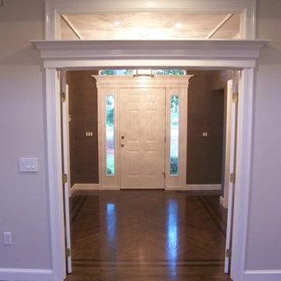 Inspiration pour un hall d'entrée traditionnel de taille moyenne avec un mur vert, un sol en bois foncé, une porte simple et une porte blanche.